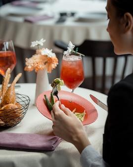 Mujer comiendo una ensalada verde con aguacate en el restaurante.