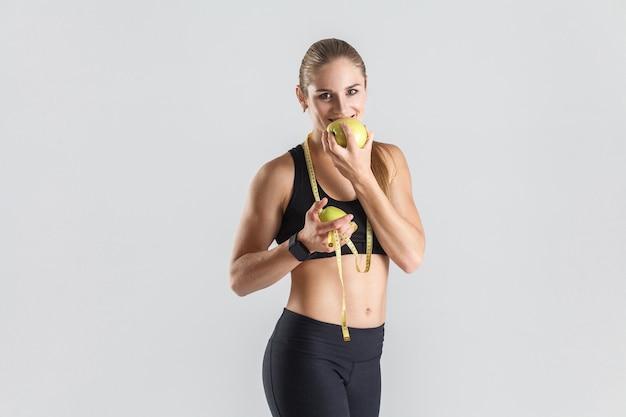 Mujer comiendo manzana verde toothy sonriendo y mirando a la cámara