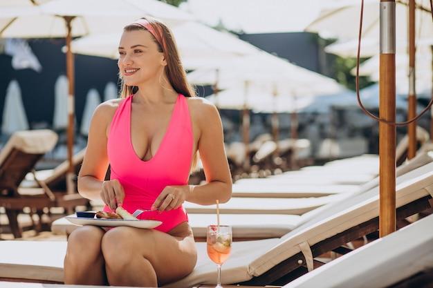 Mujer comiendo nalysnyki ucraniano junto a la piscina