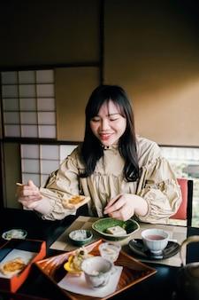 Mujer comiendo con palillos de tiro medio