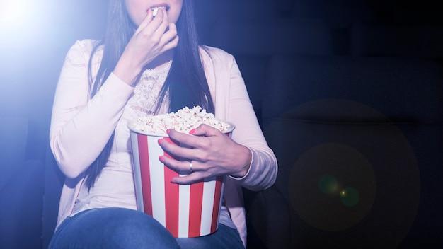 Mujer comiendo palomitas en cine