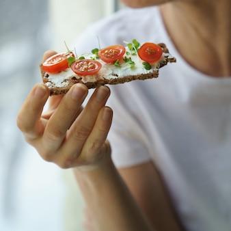 Mujer comiendo pan crujiente de centeno con cremoso queso vegetariano tofu tomate micro verdes alimentos saludables