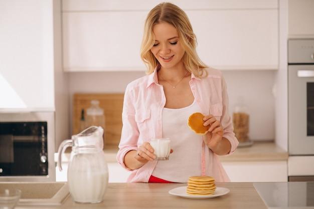 Mujer comiendo panqueques con leche