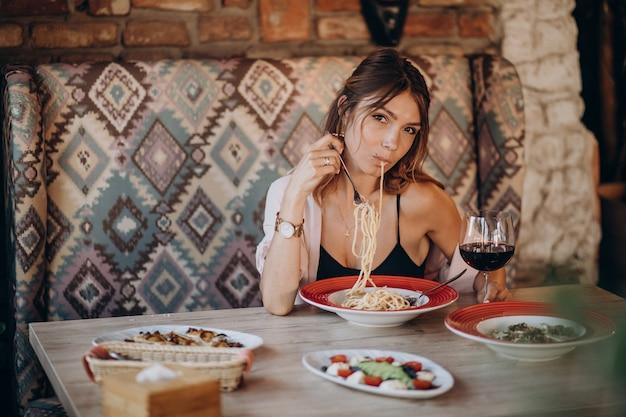Mujer comiendo pasta en un restaurante italiano