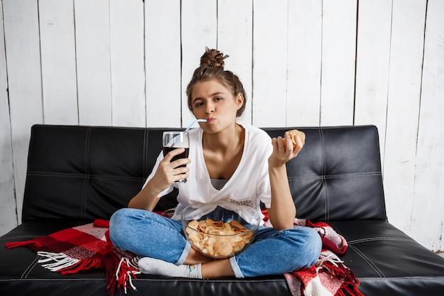 Mujer comiendo patatas fritas, bebiendo refrescos, viendo televisión, sentado en el sofá.