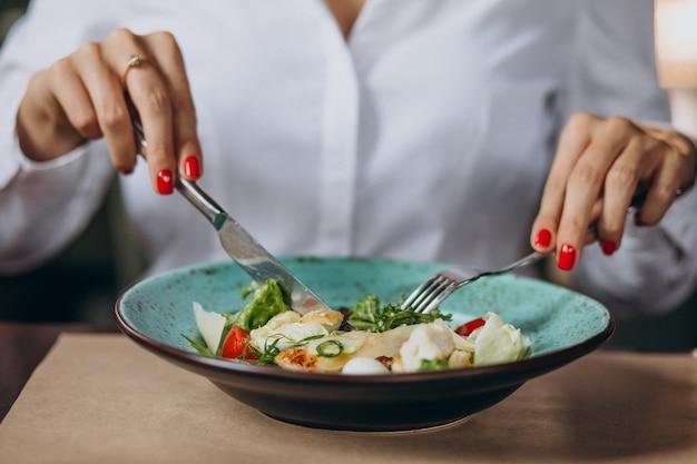 Mujer comiendo plato de ensalada