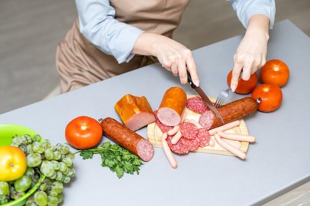 Mujer comiendo salchichas en la cocina
