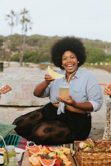 Mujer comiendo una sandía en un picnic en la playa