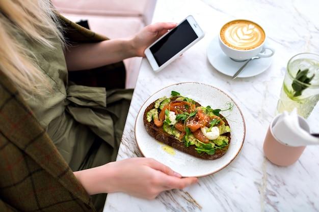 Mujer comiendo su sabroso brunch en la cafetería hipster, vista superior de la mesa de mármol, tostadas de salmón y aguacate, café y pasteles de queso sabrosos dulces, disfrutando de su desayuno.