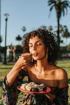 Mujer comiendo sushi en el parque