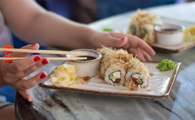 Mujer comiendo sushi con salsa de soja, wasabi y palos en restaurante.