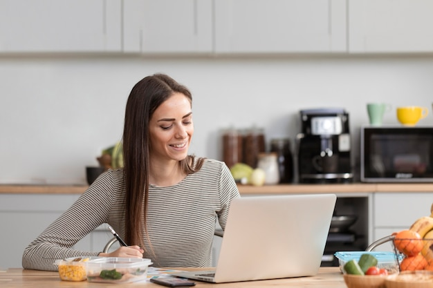 Mujer comiendo y teletrabajando