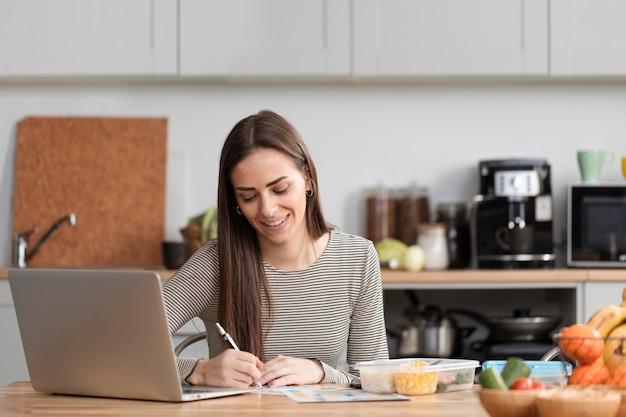 Mujer comiendo y trabajando a distancia