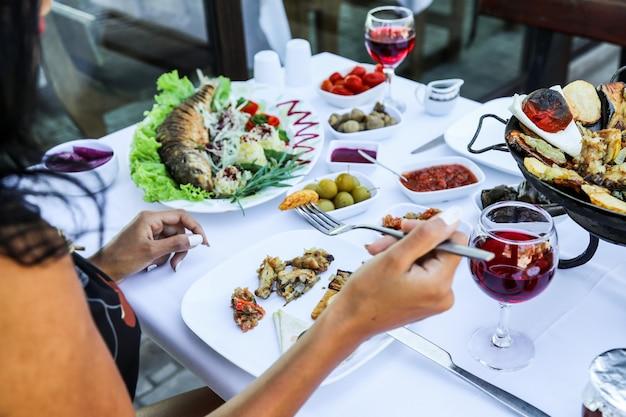Mujer comiendo varios alimentos mientras está sentado en el restaurante