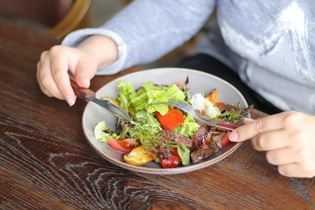 La mujer está comiendo verduras saludables y ensalada de carne con cuchillo y tenedor en la mesa de madera