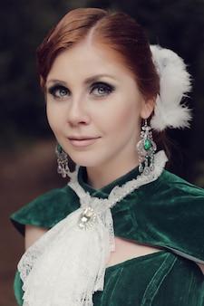 Una mujer como una princesa con un vestido vintage en el parque de las hadas