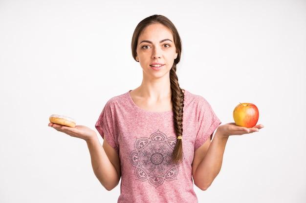 Mujer comparación donut y manzana
