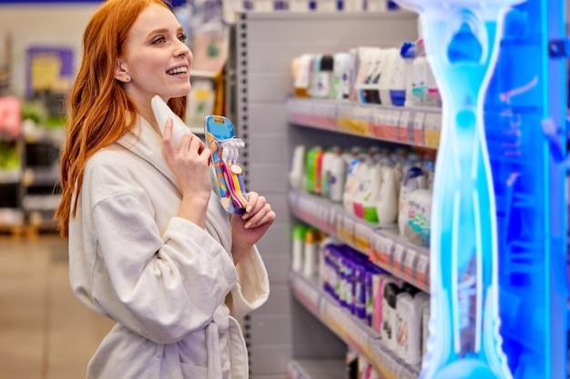 Mujer comparando la máquina de afeitar eléctrica y convencional elegir antes de realizar la compra stand en el pasillo de la tienda disfrutando de compras, vistiendo albornoz