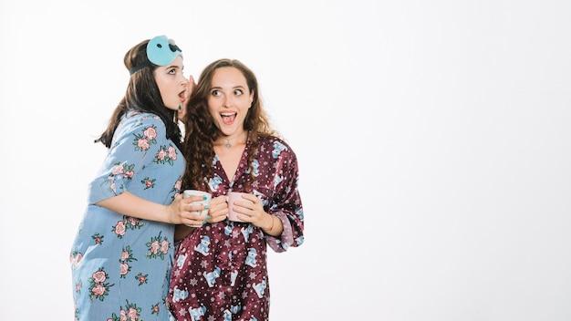 Mujer compartiendo secreto con su amiga mientras toma café