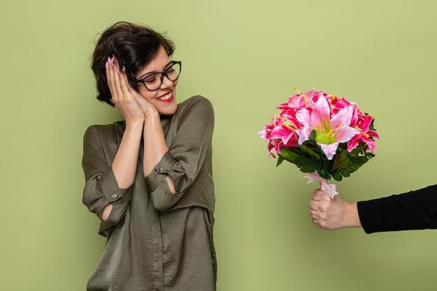 Mujer complacida con cabello corto mirando sorprendida y feliz sonriendo alegremente mientras recibe un ramo de flores de su novio celebrando el día internacional de la mujer el 8 de marzo.