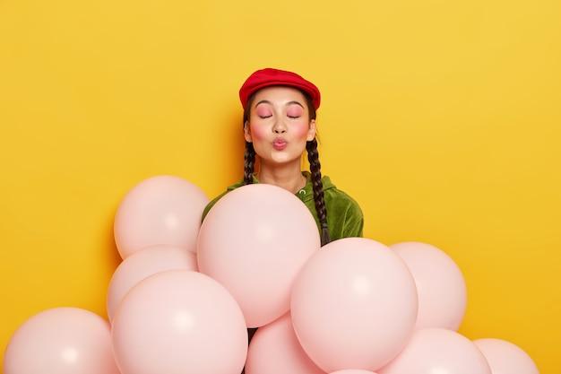 Mujer complacida con maquillaje rosa, mantiene los labios redondeados, quiere besar a los invitados, está agradecida por venir a la fiesta, se para cerca de globos, usa boina roja de moda