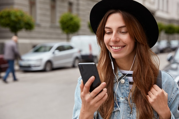 Mujer complacida con sombrero, sostiene el teléfono celular en la mano, escucha música de la lista de reproducción, pasea durante el tiempo libre por el entorno urbano