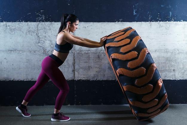 Mujer de complexión muscular que se resuelve en el gimnasio volteando el neumático del camión