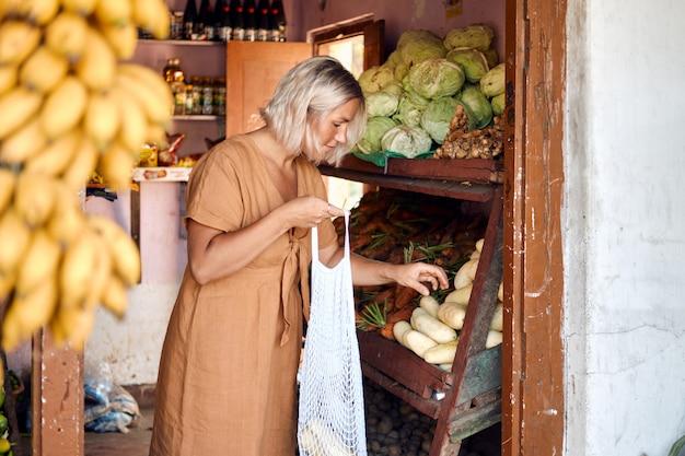 Mujer compra fruta fresca en el exótico mercado local