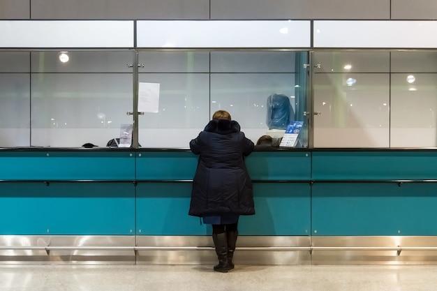 Mujer compra de pase en recepción operada. verificación en control aduanero. cambio de moneda en el aeropuerto. comprando un boleto en un pequeño quiosco en el interior. anciana en la recepción. ayudar.