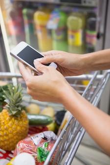 Mujer compra productos y usa su smartphone.