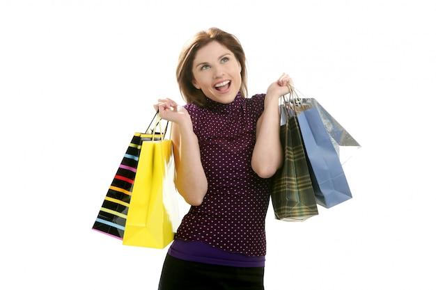 Mujer compradora compulsiva con bolsos de colores sobre blanco
