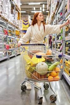 Mujer comprando alcohol en la tienda, eligiendo vacaciones, comprando sola en bata de baño