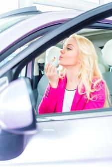 Mujer comprando un coche en el concesionario y corrigiendo el maquillaje en el espejo