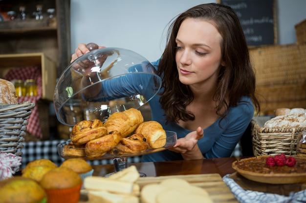 Mujer comprando croissant en el mostrador de la panadería