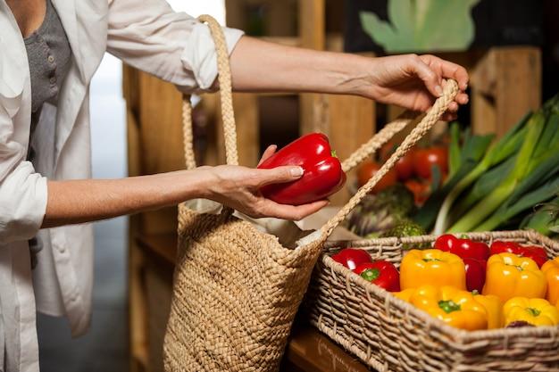 Mujer comprando pimiento en la sección orgánica