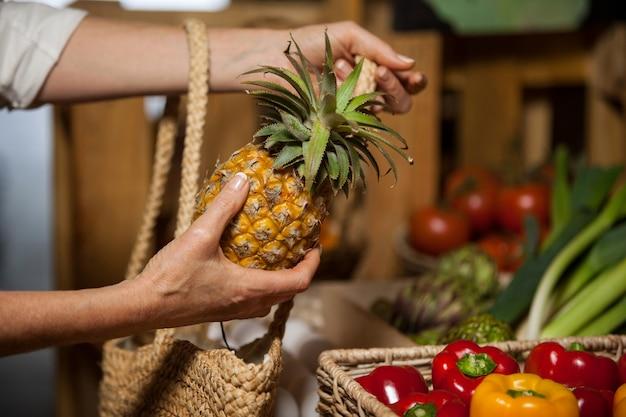 Mujer comprando piña en la sección orgánica