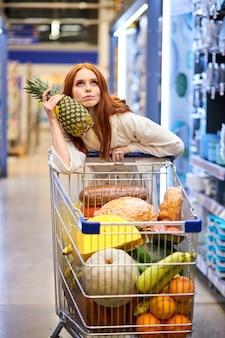 La mujer está comprando piña en la tienda, vistiendo albornoz, la mujer está comprando, pensando de pie