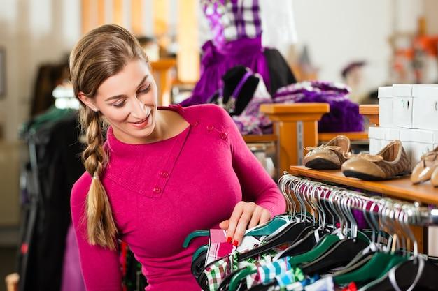 Mujer está comprando tracht o dirndl en una tienda.
