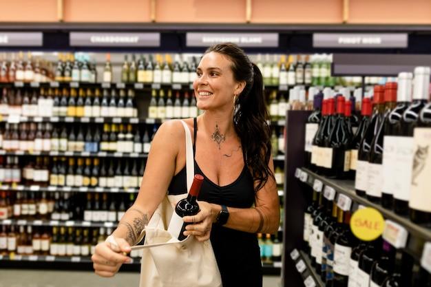 Mujer comprando vino, supermercado compras imagen hd