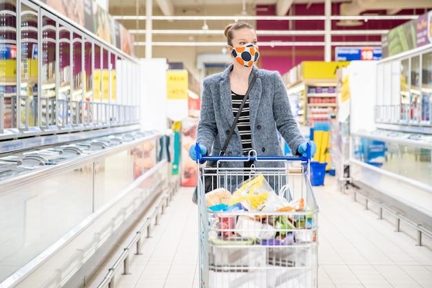 Mujer comprando víveres en un supermercado durante una epidemia de coronavirus con una máscara médica en la cara