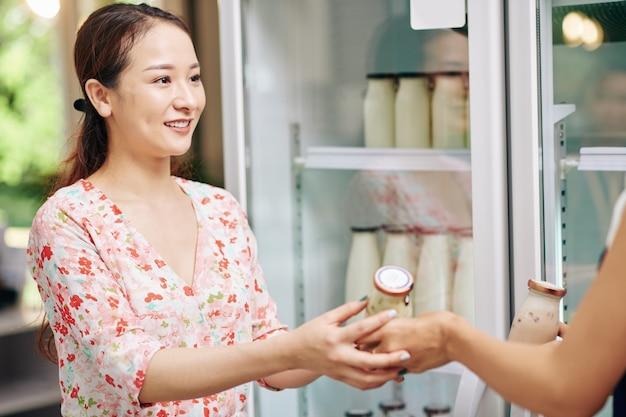 Mujer comprando yogur orgánico fresco