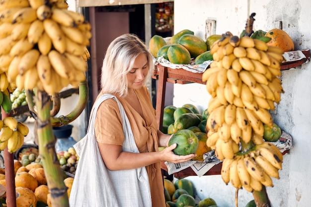 Mujer comprar papaya fresca en el mercado local tropical
