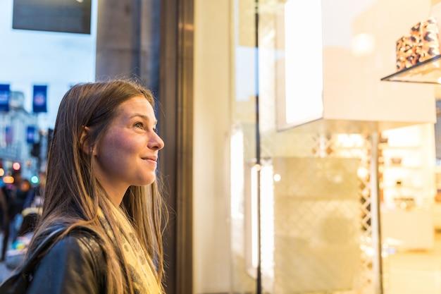Mujer de compras en londres y mirando a un escaparate