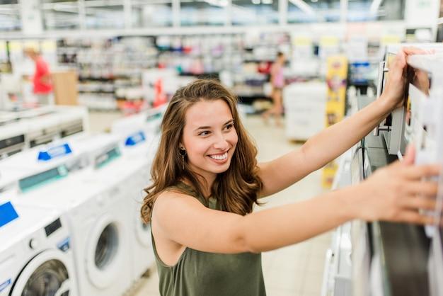 Mujer de compras para microondas en la tienda de electrodomésticos.