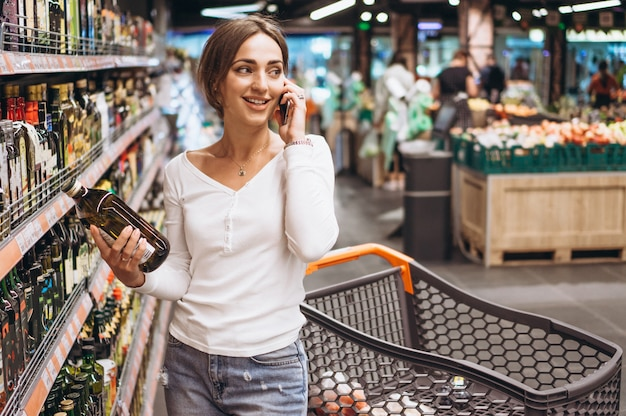 Mujer de compras en el supermercado y hablando por teléfono