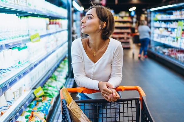 Mujer de compras en la tienda de comestibles, junto al refrigerador