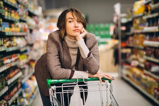 Mujer de compras en la tienda de comestibles