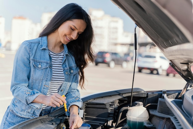 Mujer comprobando el aceite de su coche