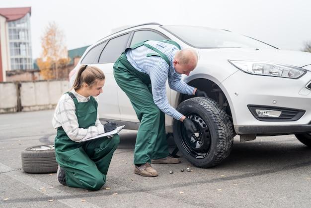 Mujer comprobando cómo el trabajador cambia la rueda de un coche