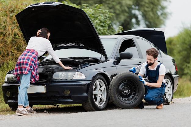 Mujer comprobando motor y hombre cambiando neumáticos